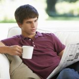 Teenage Boy Relaxing On Sofa With Newspaper And Drink