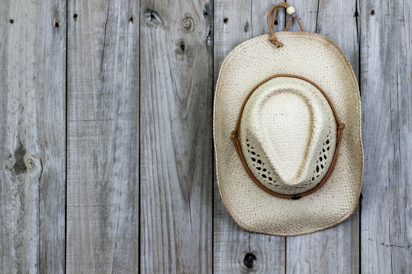 Cowboy hat hanging on rustic wood background