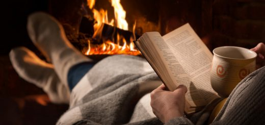 Woman resting with cup of hot drink and book near fireplace. Bild: Alexander Raths / Fotolia.com